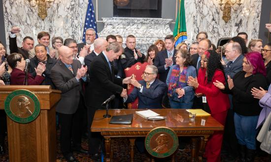 Governor Inslee takes a pen as he prepares to sign the Use of Deadly Force bill during the 2019 legislative session. He is surrounded by legislators, community members and advocates who support the legislation.