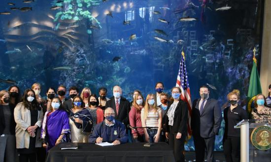 Photo of Gov. Inslee and stakeholders in front of a large fish tank at the Seattle Aquarium