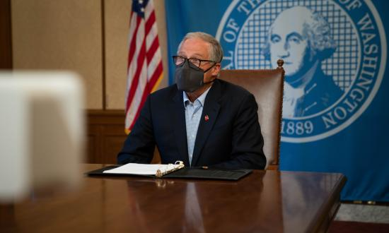 Gov. Inslee, in a face mask, seated at a press conference